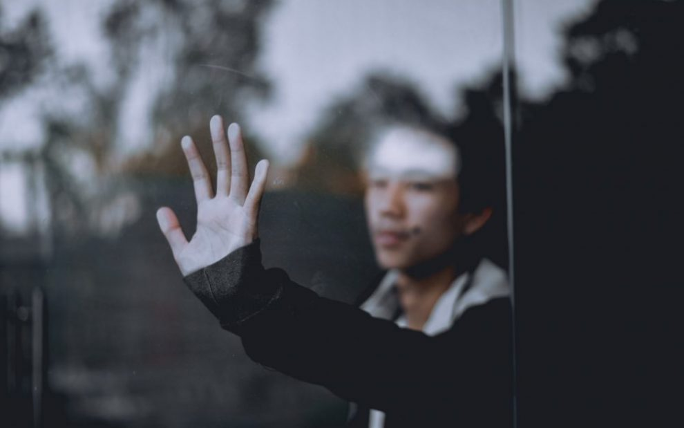 man-looking-through-a-window-with-hand-on-glass