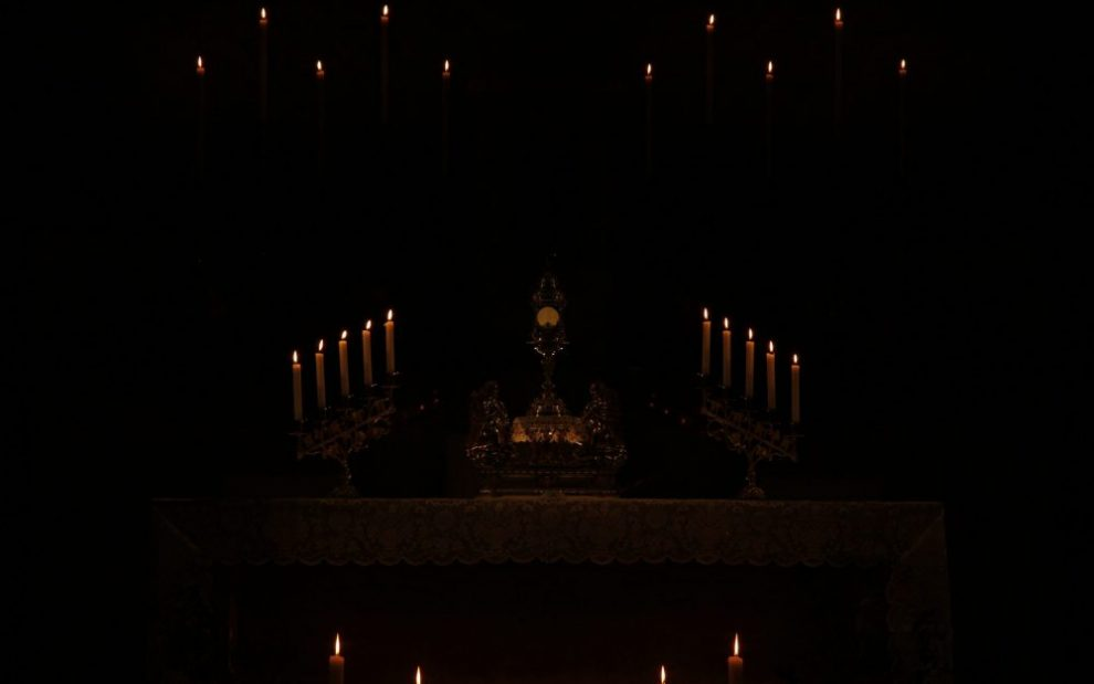 a-host-ina-monstrance-lit-by-candles