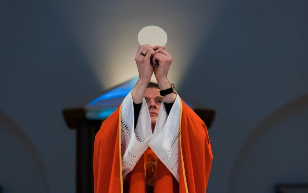 priest-lifting-up-eucharist-at-altar-during-mass