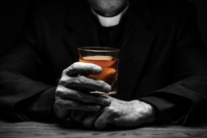 priest-holding-glass-of-whiskey