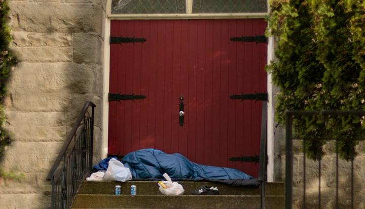 person-sleeping-bag-church-steps-red-door