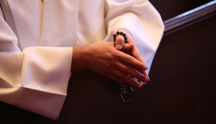 priest-praying-rosary