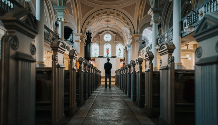 lone-figure-stands-between-pews-facing-altar