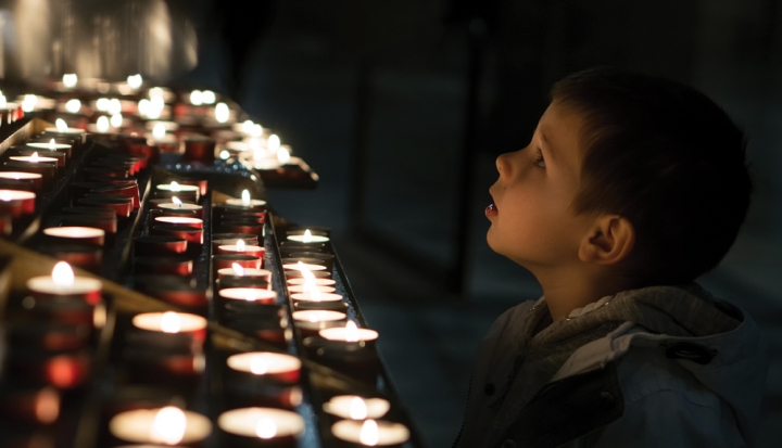 boy-stands-in-front-of-votive-candles