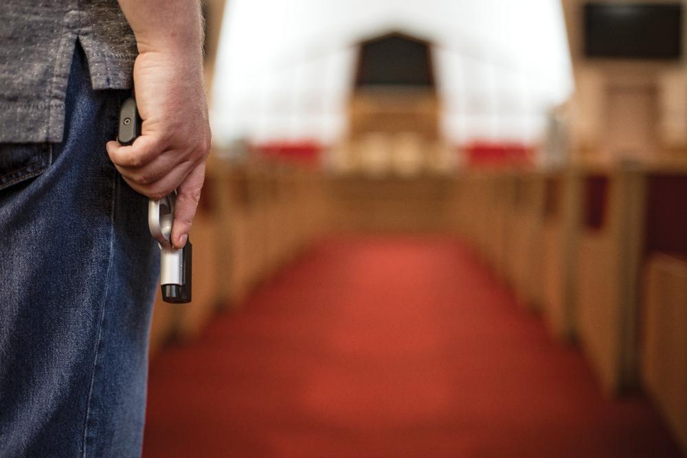hand-holding-gun-in-church
