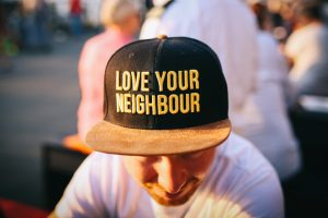 man-wearing-hat-that-says-love-your-neighbour