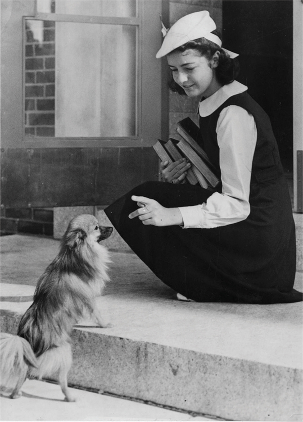 child-wearing-uniform-greets-small-dog