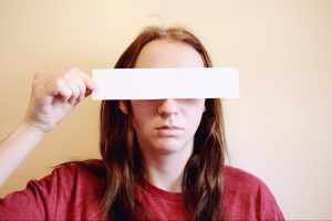 woman-red-shirt-paper-over-eyes