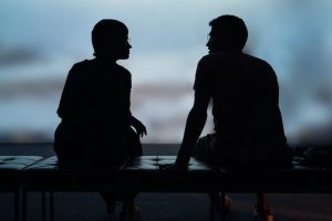 two-silhouette-people-talking
