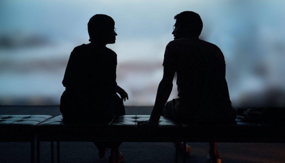 two-silhouette-people-talking
