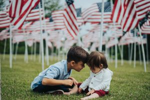 two-kids-on-grass-with-american-flags