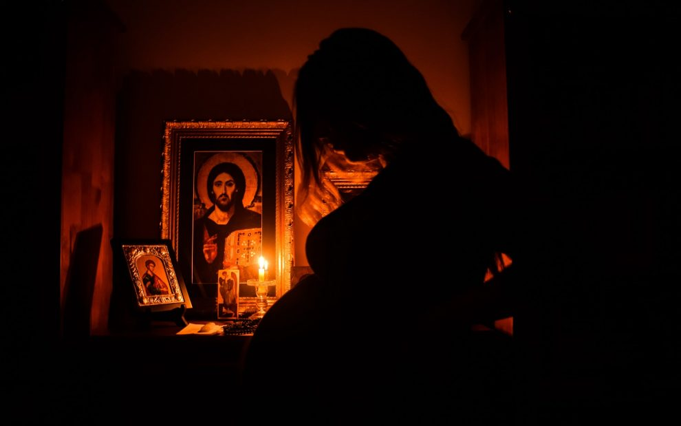 silhouette of pregnant woman beside altar