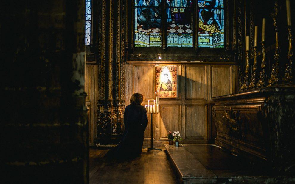 dark-church-woman-praying-in-front-of-tabernacle