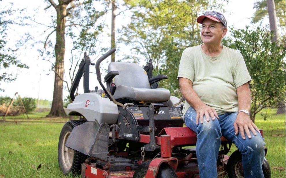 father-ron-foshage-sitting-on-a-riding-lawn-mower