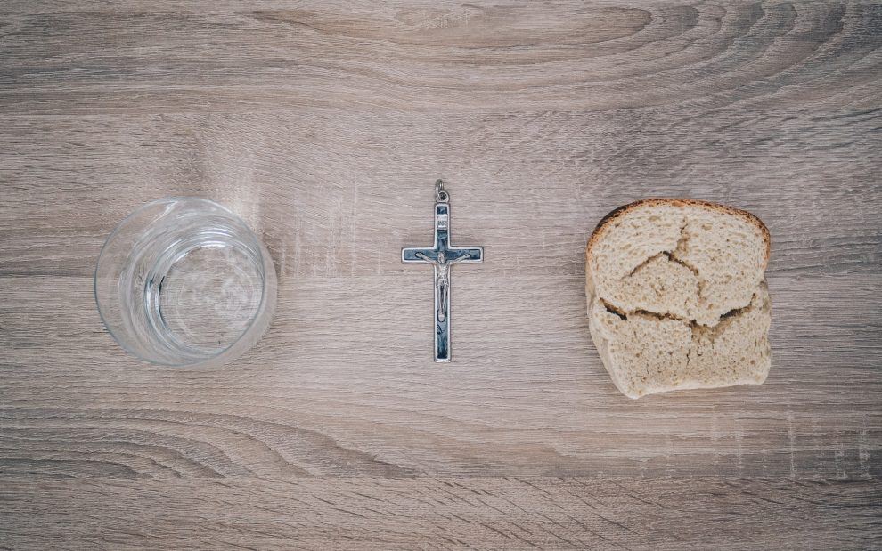 close-up-of-silver-cross-bread-and-cup-of-water