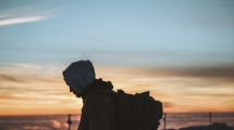 man-in-hoodie-with-backpack-looking-at-sunset