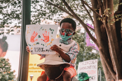 young-black-boy-sitting-on-shoulders-holding-sign