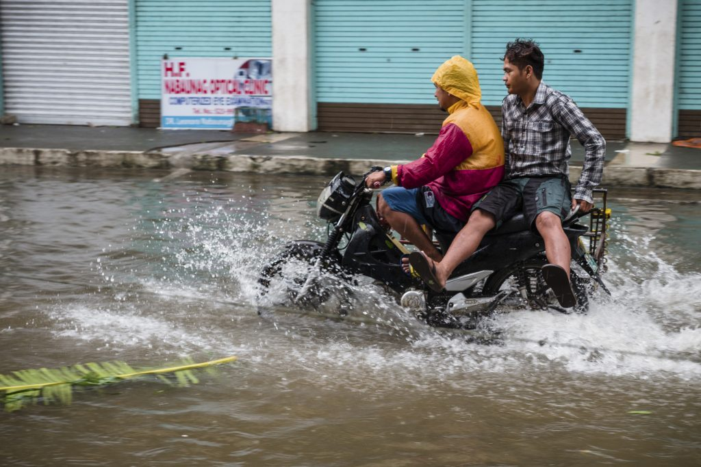 two-men-ride-a-motorcycle-through-floods-after-a-typhoon