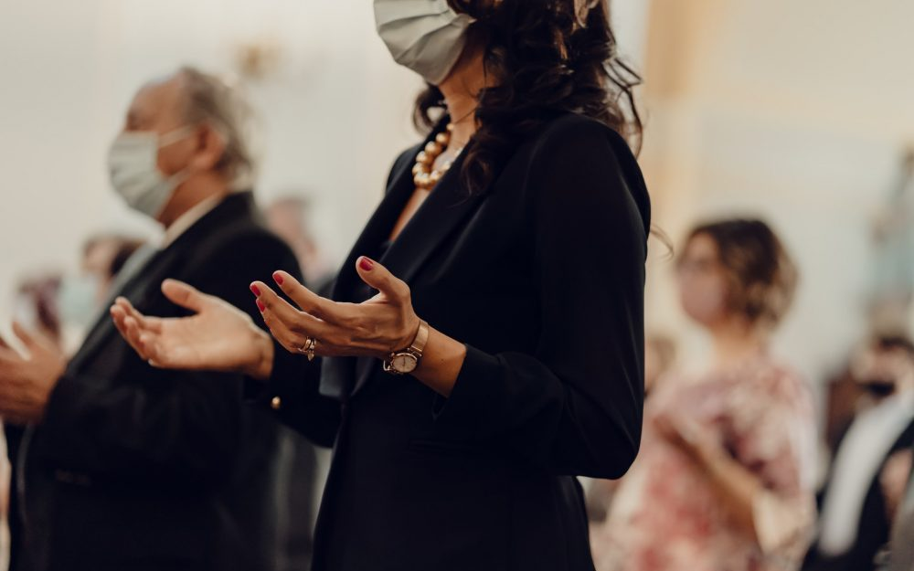 woman-in-mask-holding-up-hands-in-prayer