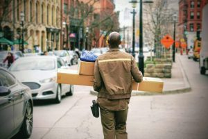 worker-carrying-packages-on-sidewalk