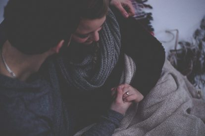couple-embracing-under-grey-blanker