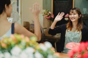 women-waving-to-each-other-in-a-florist-shop