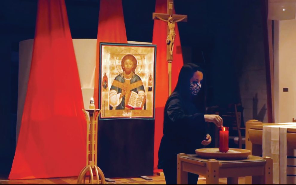 woman-lighting-a-candle-for-taize-prayer