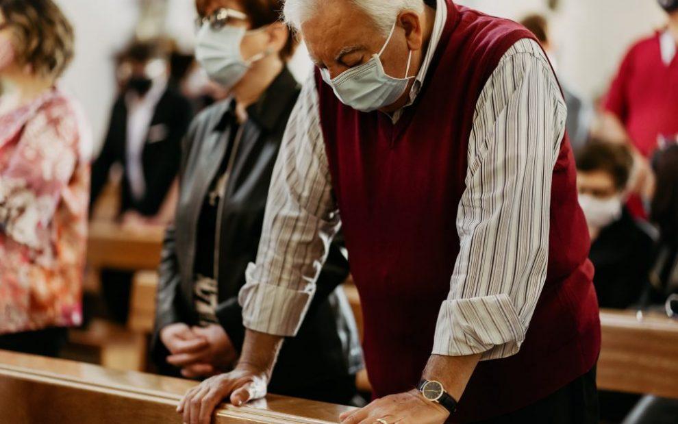 man-wearing-mask-praying-in-pew