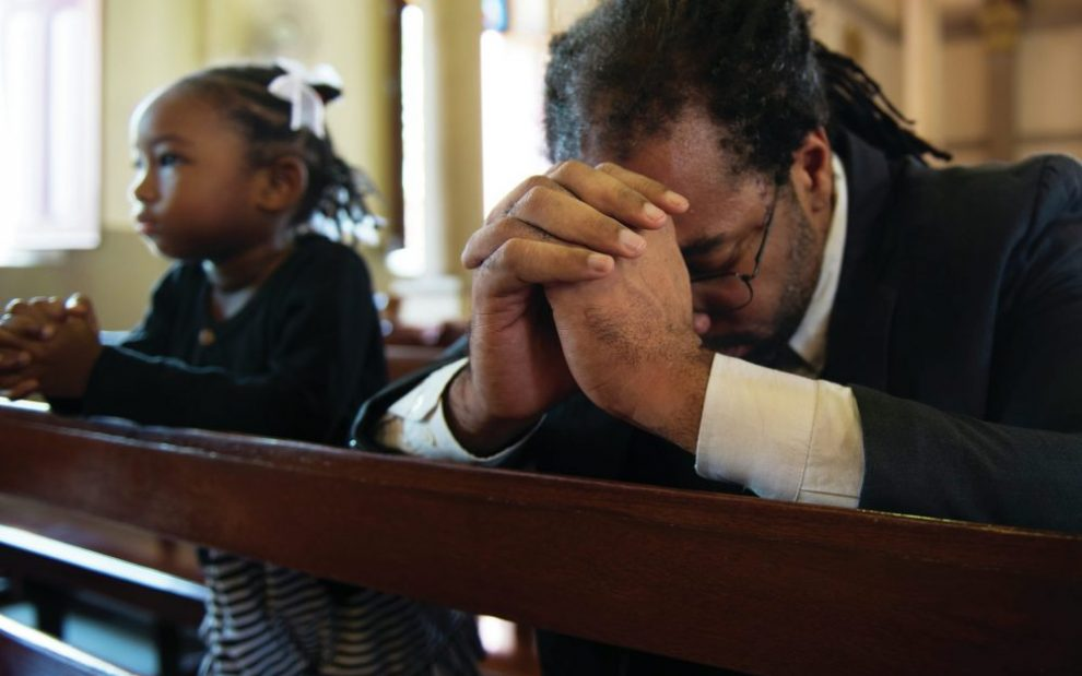black-father-and-daughter-praying-in-pews