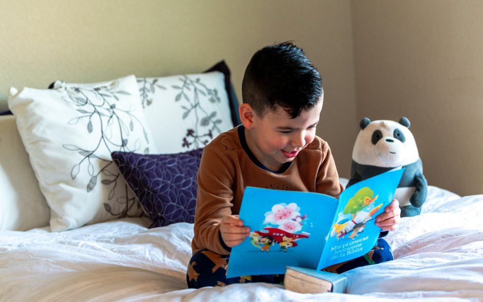 boy-reading-picture-book-in-bed