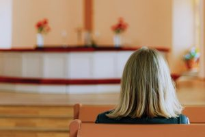 woman-sitting-alone-in-pews