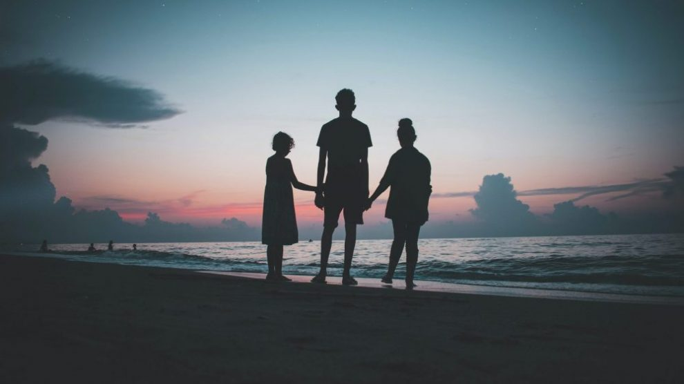 silhouette-of-three-people-standing-on-a-beach