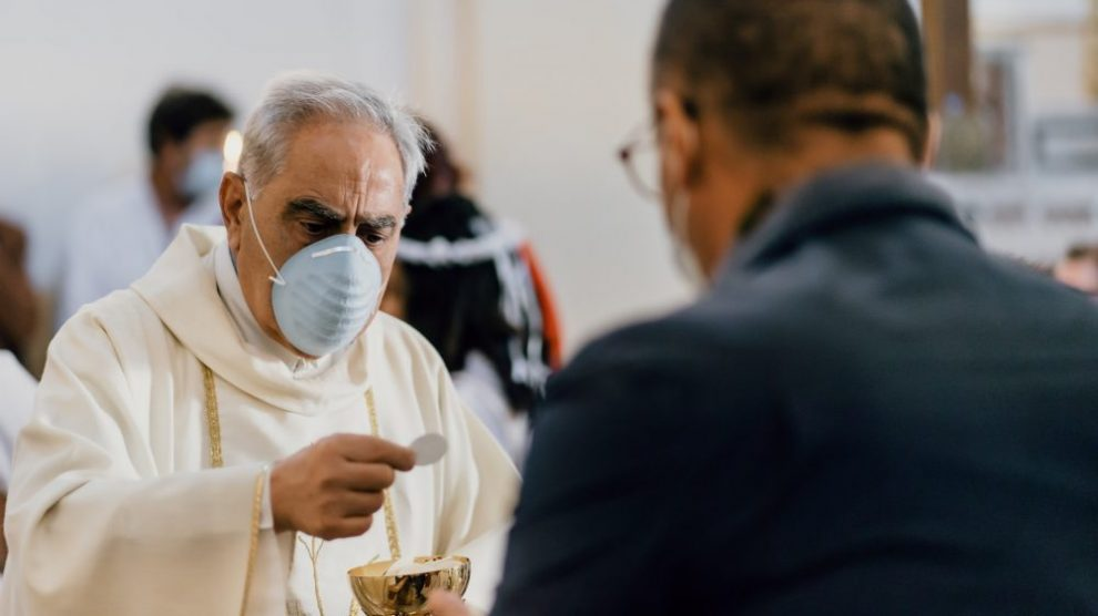 priest-in-mask-distributing-communion