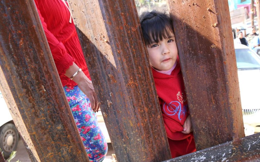 child-peeking-through-border-wall