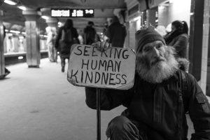 man-holding-sign-seeking-human-kindness